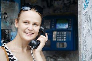 Attractive woman using a public tele