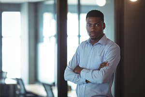 Businessman standing with arms crossed in office