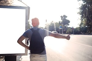 Man standing near bus stop thumbing