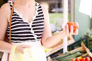 Young woman shopping for  tomatoes