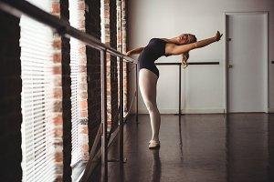 Ballerina practicing ballet dance at barre