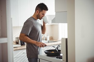 Man drinking coffee while cooking in kitchen