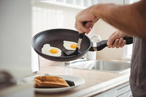 Man picking up fried eggs from cooking pan in kitchen