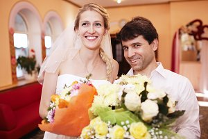 Smiling bride and groom with bouquet