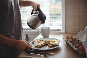 Man holding his breakfast plate while pouring hot water into mug