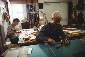 Craftswoman hammering leather