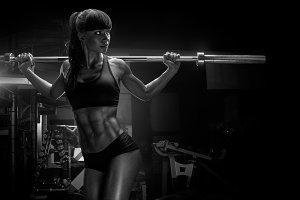 Fit and muscular female model in gym