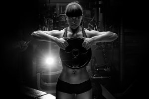 Fit female model with barbell plate