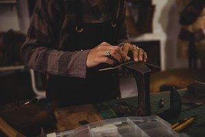 Craftswoman hammering leather in workshop
