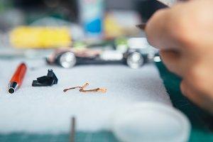 Person handcrafting miniature auto