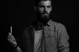 Bearded man with straight razor
