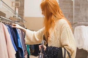 Woman chooses dress in shop
