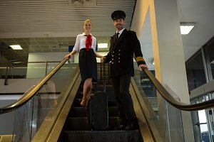 Pilot and air hostess with their trolley bags standing on escalator