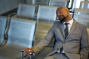 Businessman sleeping in waiting area