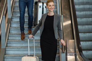 Businesspeople with luggage walking downstairs beside escalator