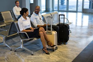 Passengers with suitcase interacting at waiting area