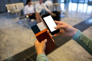 Woman hands holding Smartphone, passport and boarding pass