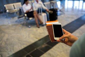 Woman hand holding Smartphone, passport and boarding pass
