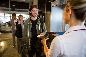 Man in queue receiving passport and boarding pass