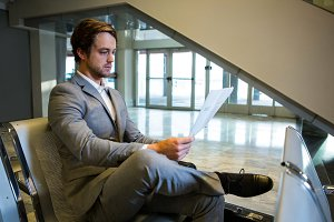 Businessman sitting with legs crossed while reading newspaper