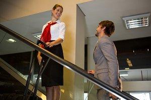 Female staff interacting with businessman on escalator