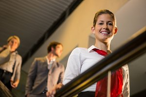 Portrait of smiling female staff standing on escalator