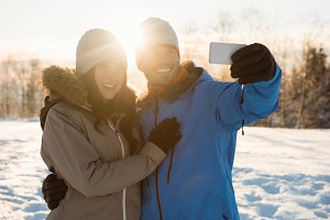 Happy couple taking a selfie on snowy landscape