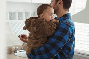 Father holding his baby while standing in kitchen
