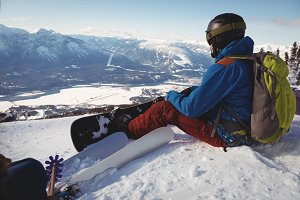Skier relaxing on snow landscape