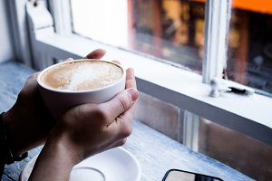 Hand of woman holding cup of coffee in café