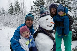 Portrait of happy parents and children with snowman