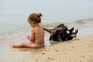 naked little girl plays in the sea, beautiful beach