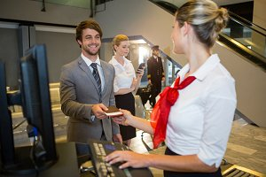 Businessman giving his boarding pass to the female staff at the check in desk