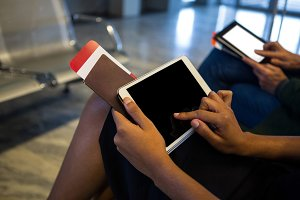Woman using digital tablet in waiting area at airport