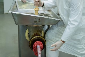 Butchers using a meat mincing machine at meat factory