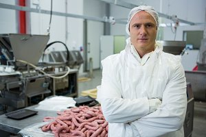 Male butcher standing with arms crossed