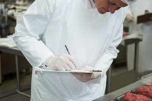 Male butcher maintaining records on clipboard
