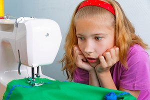 Teen girl frightened by her mistake when sewing