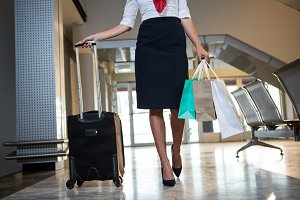 Airhostess walking with trolley bag and shopping bags