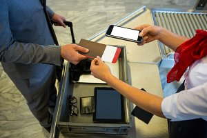 Female airport staff using mobile phone to scan the passport