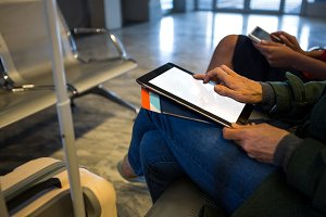 Woman using digital tablet in waiting area