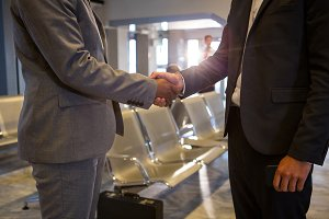 Business people shaking hands in airport terminal
