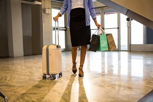 Business woman walking with luggage and shopping bag