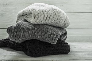 warm knitted sweater, three pieces, black, grey and white on a wooden background