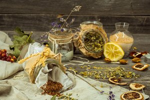 Cup of tea on wooden background with lemon and herbs