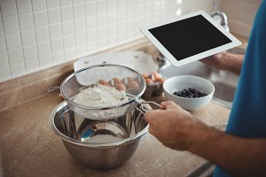 Man sifting flour into a mixing bowl while using a digital tablet