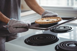 Man holding a tray of freshly baked tart in kitchen