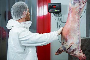 Butcher weighing raw meat