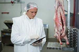 Male butcher maintaining records on digital tablet
