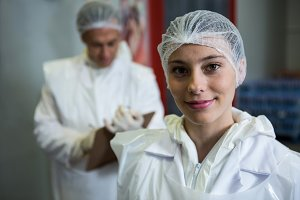 Female butcher smiling at meat factory